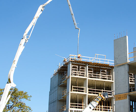 Concrete pumping boom placing concrete for a high rise building | Commercial Services